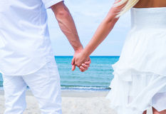 Loving couple walking and embracing on the beach. Loving couple walking and embracing on a tropical summer beach Royalty Free Stock Photos