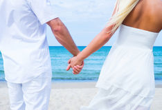 Loving couple walking and embracing on the beach. Loving couple walking and embracing on a tropical summer beach Stock Image