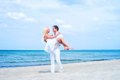 Loving couple walking and embracing on a summer beach. Loving couple walking and embracing on a tropical summer beach Stock Image
