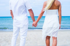 Loving couple walking and embracing on a summer beach. Loving couple walking and embracing on a tropical summer beach Royalty Free Stock Photography