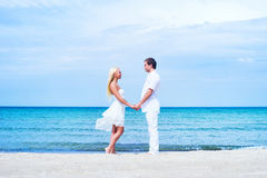 Loving couple walking and embracing on a summer beach Stock Images