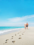 Loving couple walking with footprints at sea Royalty Free Stock Photography