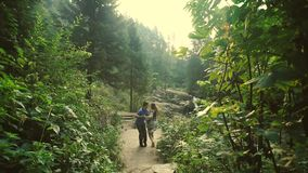 Loving Couple Walking Outdoors Near a Waterfall. Morning light shines into the camera stock video footage