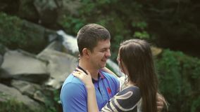 Loving Couple Walking Outdoors Near a Waterfall. Morning light shines into the camera. Slow morion stock footage