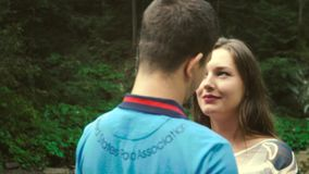 Loving Couple Walking Outdoors Near a Waterfall. Morning light shines into the camera. Slow motion stock video footage
