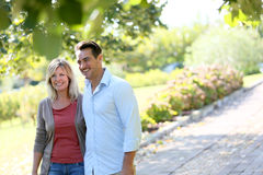 Loving couple walking in the park. Couple walking hand in hand in park Stock Images