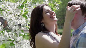 Loving couple walking in a park near a blossoming tree stock video