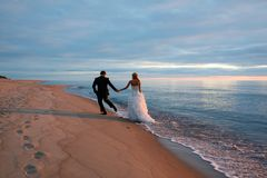 A loving couple walking by the sea coast Stock Image