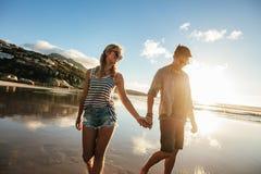 Loving couple walking on sea shore holding hands. Outdoor shot of loving young couple walking on the sea shore holding hands. Young men and women walking on the Stock Images