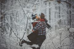 Loving couple walking in snowy winter forest Stock Photos
