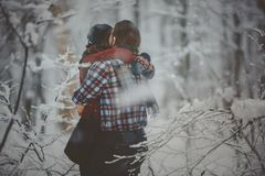 Loving couple walking in snowy winter forest Royalty Free Stock Image