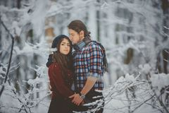 Loving couple walking in snowy winter forest Stock Photo