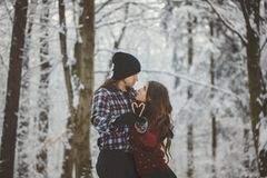 Loving couple in snowy winter forest Royalty Free Stock Images