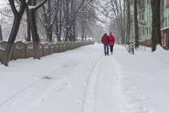 Loving couple walks alongside on an empty street despite of snow and cold Stock Photo