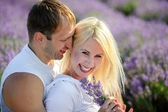 Happy couple in a field of lavender. A loving couple walks in the field of lavender, dreams and smiles. They are happy together and love each other royalty free stock images