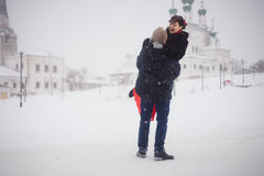 A loving couple walks in winter on the background of historical sights Stock Image