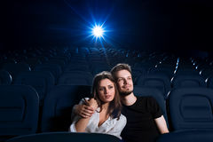 Loving couple watching a movie in the empty cinema Stock Images