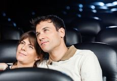 Loving Couple Watching Movie In Theater Stock Photography
