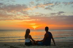 Couple watching the sunset on the beach Stock Image