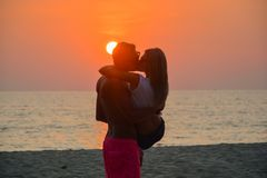 A loving couple watching the sunset on the beach stock photography