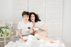 Loving couple watching TV in bed. And eating popcorn. The concept of love and romance. Toning Royalty Free Stock Photography