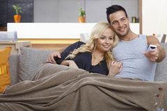 Loving couple watching tv at home. Attractive loving couple watching tv at home, smiling happy, sitting on sofa, embracing Stock Photography