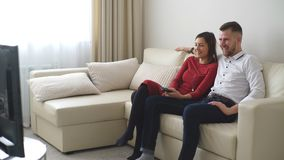 Loving couple watching TV. And smiling in hotel room stock footage