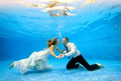 Loving couple in wedding dress swims underwater in the pool to meet each other. Horizontal view. Shooting from under the water Royalty Free Stock Photos