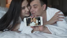 Loving couple in white coats on bed happily do selfie on a smartphone slow motion stock footage video stock video
