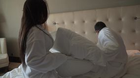 Loving couple in white coats on bed happily fights with pillows slow motion stock footage video stock footage