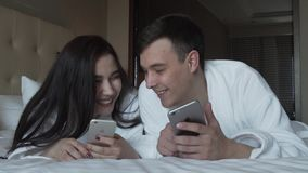 Loving couple in white coats on bed happily share information in their iPhones slow motion stock footage video stock video
