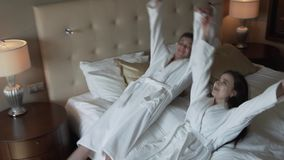 Loving couple in white coats happily jumps on bed slow motion stock footage video stock video footage