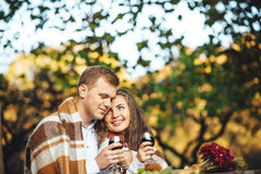 Loving couple with wine glasses embracing at the autumn park. Stock Images