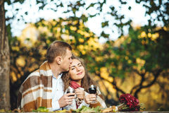 Loving couple with wine glasses embracing at the autumn park. Royalty Free Stock Photography