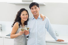 Loving couple with wine glasses in kitchen Stock Photos
