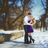 Loving couple in winter, happy guy and girl on the snow Royalty Free Stock Photos