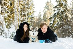 Loving couple in winter sunny forest with husky dogs in the snow. Loving couple in winter sunny forest with husky dogs Stock Photography
