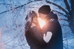 A loving couple on a winter walk. Snow love story, winter magic. Man and woman on the frosty street. The guy and the girl are rest royalty free stock image