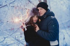 A loving couple on a winter walk. Snow love story, winter magic. Man and woman on the frosty street. The guy and the girl are rest. A loving couple on a winter Stock Photography