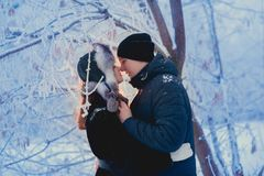 A loving couple on a winter walk. Snow love story, winter magic. Man and woman on the frosty street. The guy and the girl are rest royalty free stock photography