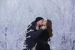 A loving couple on a winter walk. Snow love story, winter magic. Man and woman on the frosty street. The guy and the girl are rest. A loving couple on a winter Stock Image