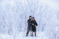 A loving couple on a winter walk. Snow love story, winter magic. Man and woman on the frosty street. The guy and the girl are rest. A loving couple on a winter Stock Photos