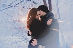 A loving couple on a winter walk. Snow love story, winter magic. Man and woman on the frosty street. The guy and the girl are rest stock photography