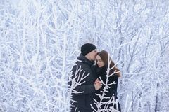 A loving couple on a winter walk. Snow love story, winter magic. Man and woman on the frosty street. The guy and the girl are rest stock photo