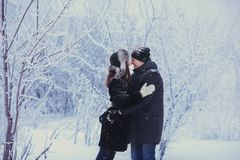 A loving couple on a winter walk. Snow love story, winter magic. Man and woman on the frosty street. The guy and the girl are rest. A loving couple on a winter Royalty Free Stock Photos
