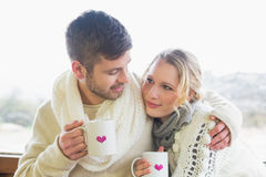 Loving couple in winter wear with coffee cups against window Royalty Free Stock Photo