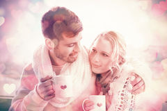 Loving couple in winter wear with coffee cups against window Stock Photo