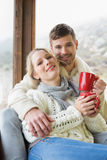 Loving couple in winter wear with cups against window Royalty Free Stock Images