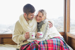 Loving couple in winter wear with cups against window Royalty Free Stock Photography