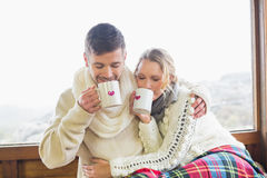 Loving couple in winter wear drinking coffee against window Stock Photos